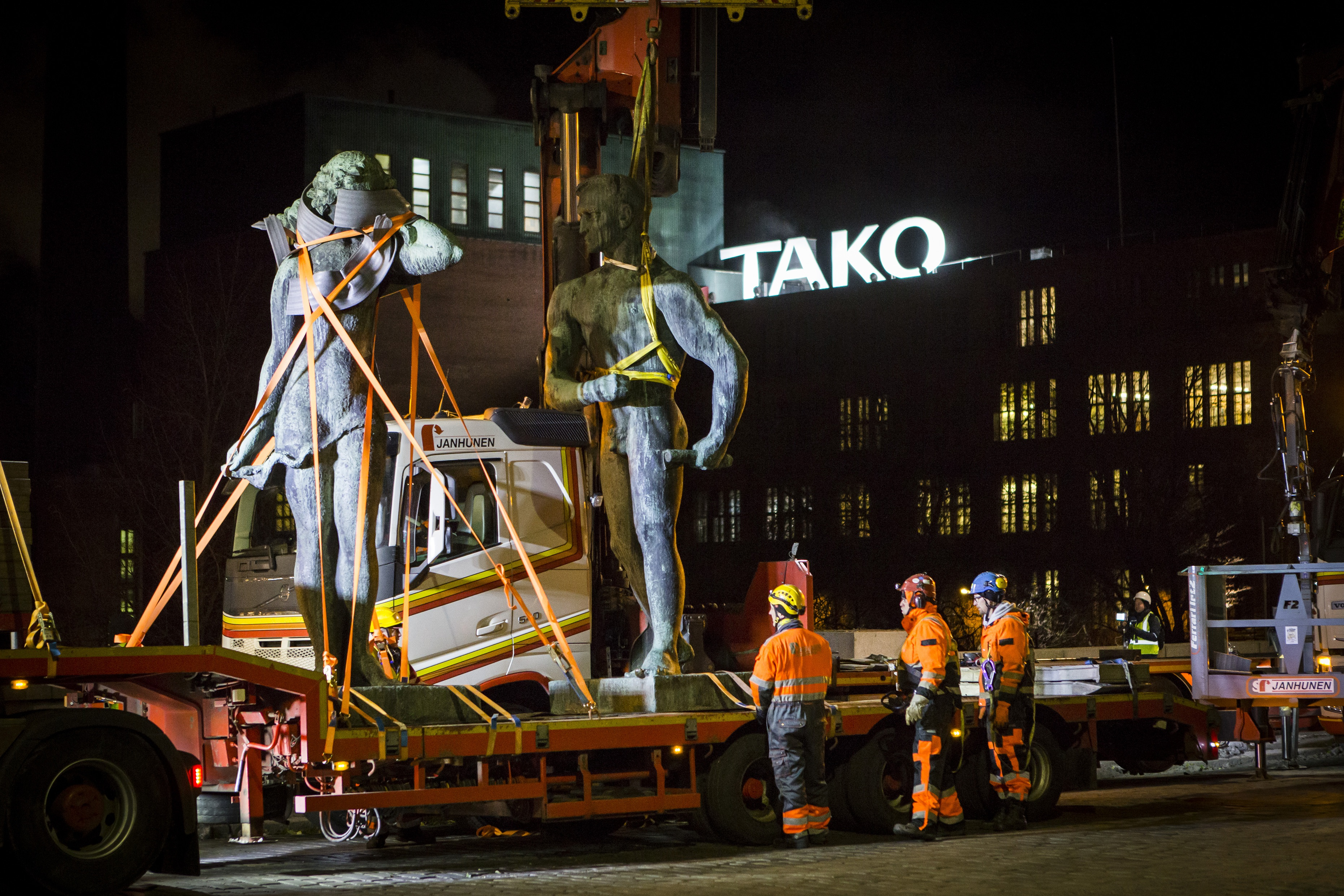 Kolme työpukuista henkilöä katsoo kun kahta isoa viestosta nostetaan kuorma-auton lavalle. Taustalla teksti TAKO tehtaan katolla.