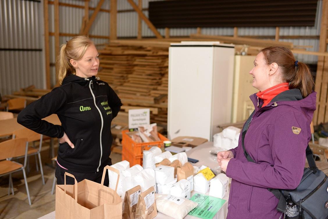 Kaksi henkilöä keskustelemassa maatilalla. Välissä myyntipöytä, jossa maatilan tuotteita.