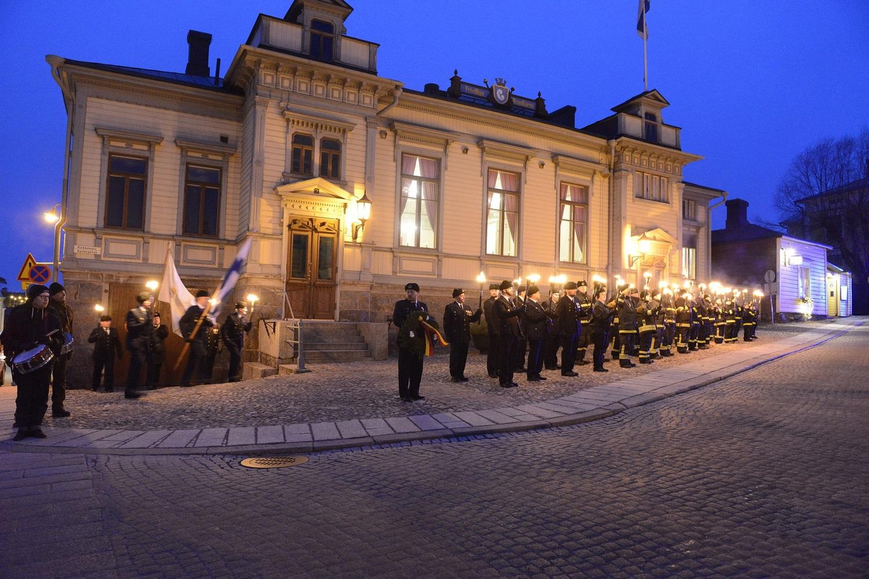 Kadun varressa useita henkilöitä uniformussa kädessään soihtu. Vasemmalta saapumassa lippukulkue ja orkesterin jäseniä. Taustalla puurakennus.
