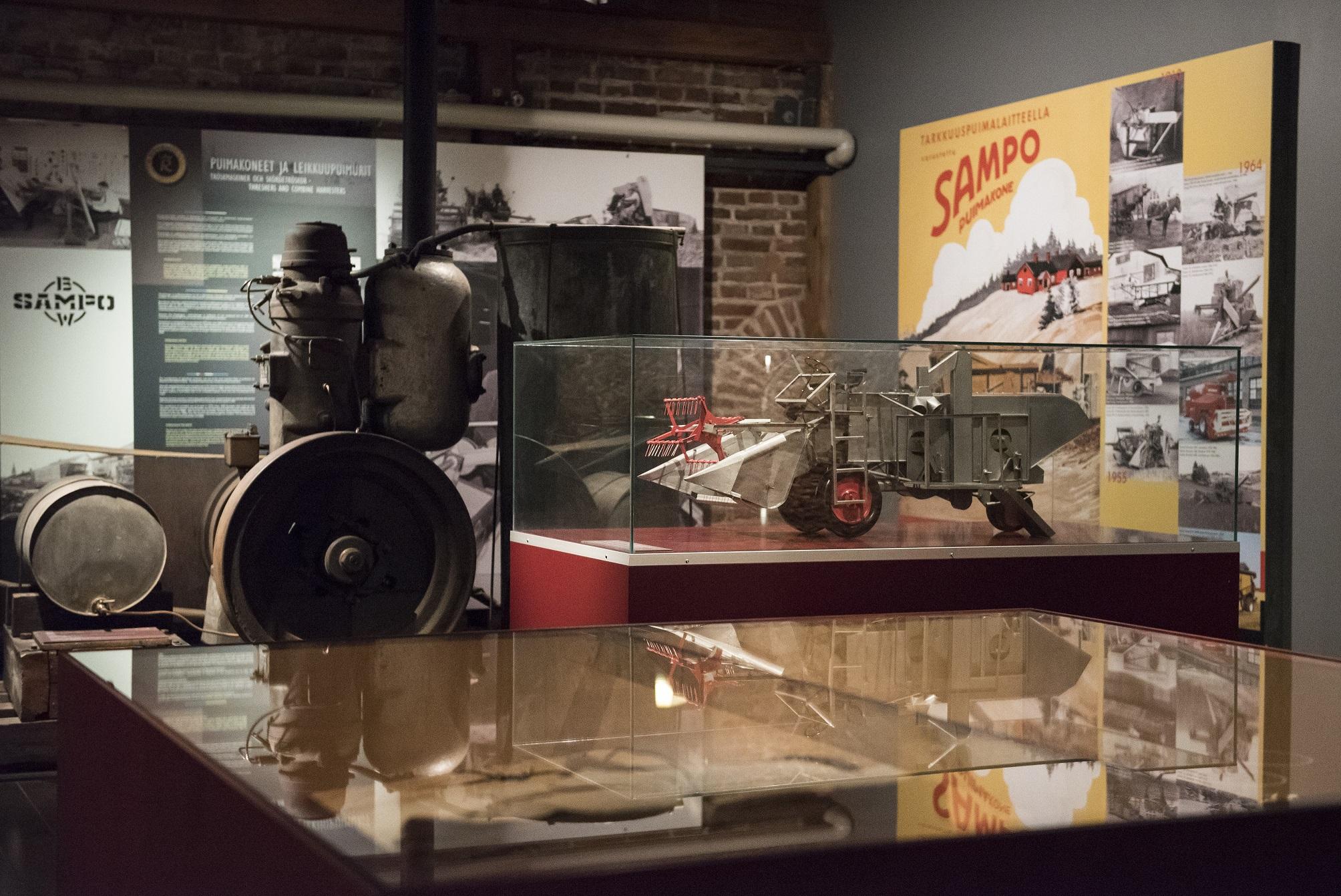 Museon näyttelytila, jonka etualalla lasivitriini ja taustalla maatalouskoneen pienoismalli, näyttelyesine ja näyttelytekstejä.