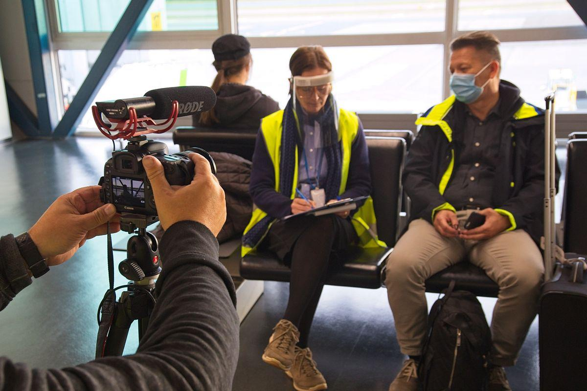 Museotyöntekijä haastattelee lentomatkustajaa, molemmat istuvat penkillä. Kuvan etualalla näkyy toisen museotyöntekjän käsi ja kamera.